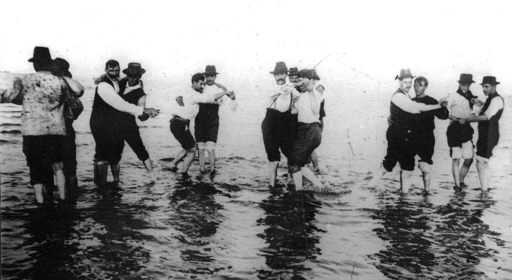Hombres bailando tango en la orilla del río.
