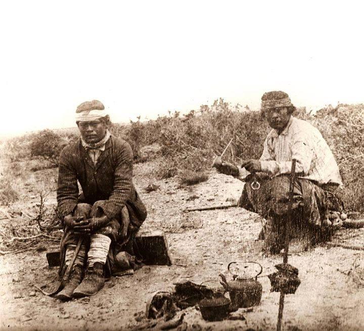 Mapuches tomando mate en la pampa mientras se asa la carne, c.1880.